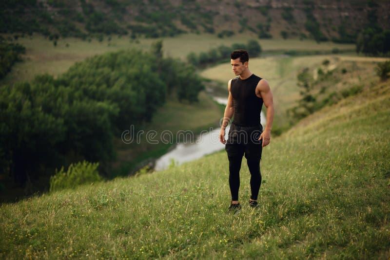 Φίλαθλο άτομο sportswear workout έξω, απομονωμένος σε ένα όμορφο υπόβαθρο τοπίων στοκ εικόνα με δικαίωμα ελεύθερης χρήσης