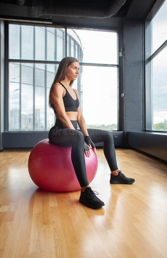 Φίλαθλο θηλυκό sportswear στη συνεδρίαση στην κατάλληλη σφαίρα στοκ εικόνα