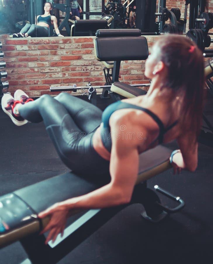Φίλαθλο κορίτσι που κάνει τα ABS β-UPS workout στη γυμναστική στοκ φωτογραφίες