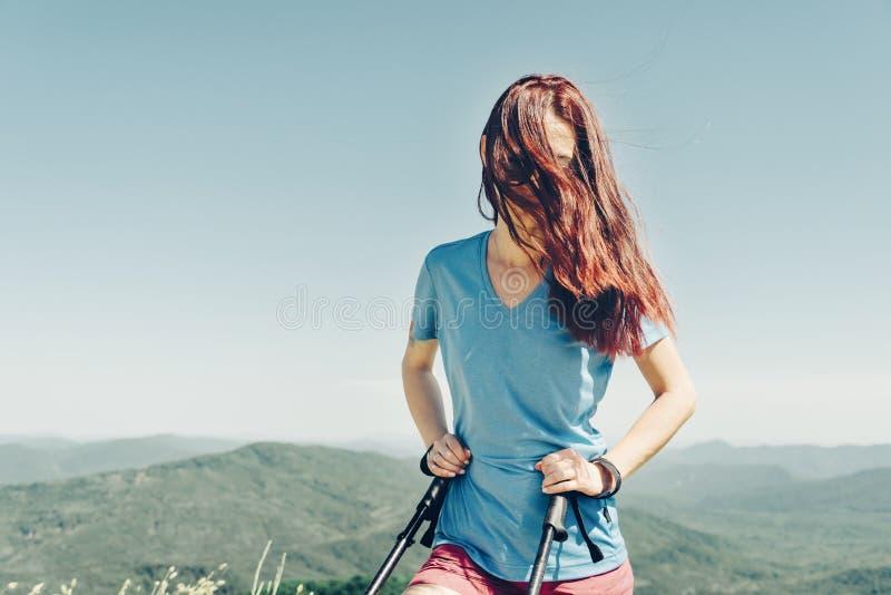 Φίλαθλο κορίτσι που περπατά με τους πόλους οδοιπορίας υψηλούς στα βουνά στοκ εικόνα
