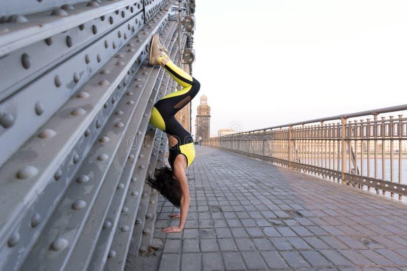 Φίλαθλο κορίτσι στη μαύρη και κίτρινη φόρμα γυμναστικής που στέκεται στην άνω πλευρά χεριών της - κάτω στη γέφυρα στο ηλιοβασίλεμ στοκ φωτογραφίες