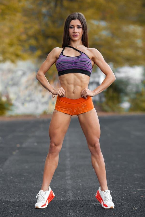 Φίλαθλο προκλητικό κορίτσι με την επίπεδη κοιλιά workout, υπαίθρια Λεπτή αθλητική γυναίκα στο στάδιο, ABS στοκ εικόνα