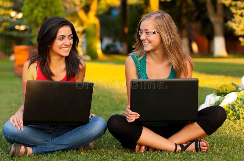 Φίλες με το κάθισμα lap-top στοκ φωτογραφία