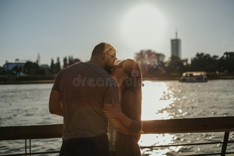 Φίλημα ζεύγους από τον ποταμό στο ηλιοβασίλεμα στοκ εικόνες