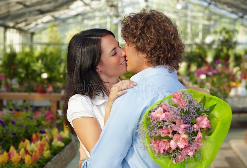 Φίλημα ζεύγους στο βρεφικό σταθμό λουλουδιών στοκ εικόνα με δικαίωμα ελεύθερης χρήσης