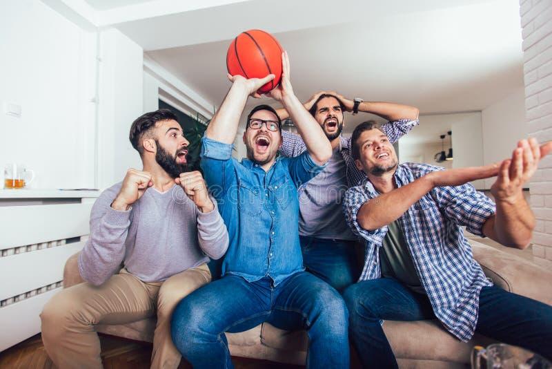 Φίλοι ή ανεμιστήρες καλαθοσφαίρισης που προσέχουν το παιχνίδι καλαθοσφαίρισης στη TV και που γιορτάζουν τη νίκη στο σπίτι Φιλία,  στοκ φωτογραφία με δικαίωμα ελεύθερης χρήσης