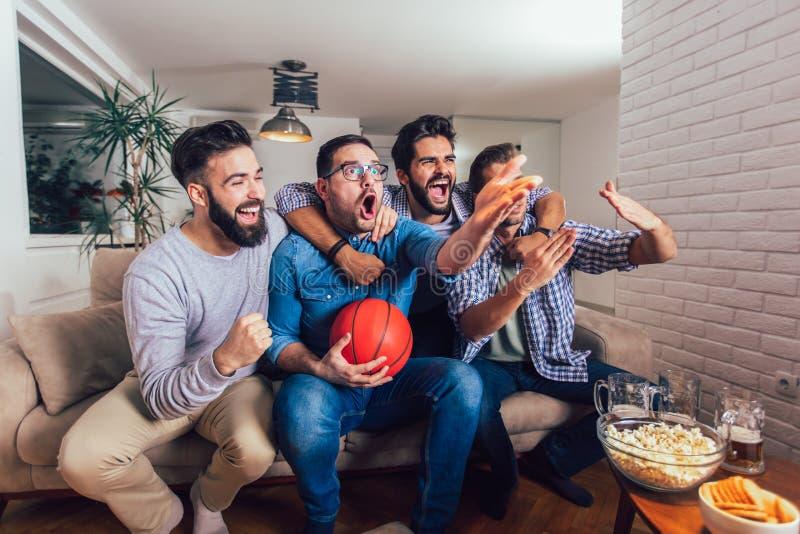 Φίλοι ή ανεμιστήρες καλαθοσφαίρισης που προσέχουν το παιχνίδι καλαθοσφαίρισης στη TV και που γιορτάζουν τη νίκη στο σπίτι Φιλία,  στοκ εικόνες με δικαίωμα ελεύθερης χρήσης