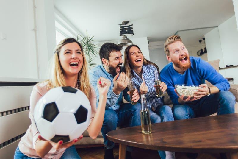 Φίλοι ή οπαδοί ποδοσφαίρου που προσέχουν το ποδόσφαιρο στη TV και που γιορτάζουν τη νίκη στο σπίτι Φιλία, αθλητισμός και έννοια ψ στοκ φωτογραφίες