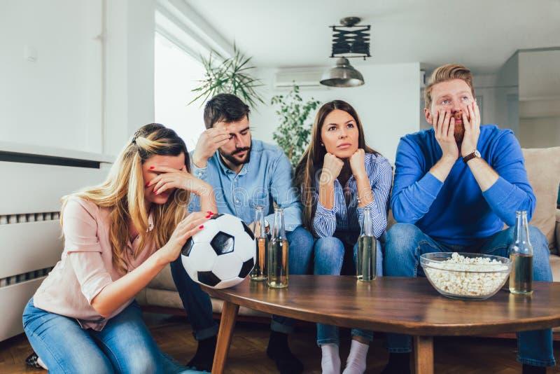 Φίλοι ή οπαδοί ποδοσφαίρου που προσέχουν το ποδόσφαιρο στη TV και που γιορτάζουν τη νίκη στο σπίτι Φιλία, αθλητισμός και έννοια ψ στοκ φωτογραφία με δικαίωμα ελεύθερης χρήσης