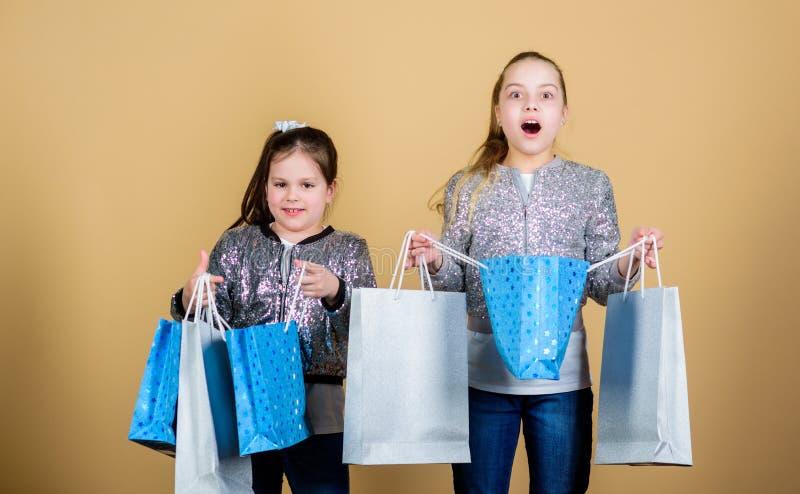 Φίλοι αδελφών κοριτσιών με το μπεζ υπόβαθρο τσαντών αγορών r Μαύρη Παρασκευή E στοκ φωτογραφίες με δικαίωμα ελεύθερης χρήσης
