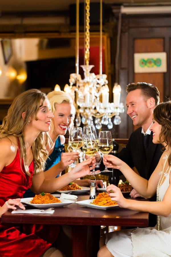 Φίλοι γυαλιά ενός στα πολύ καλά εστιατορίων κουδουνίσματος στοκ εικόνες
