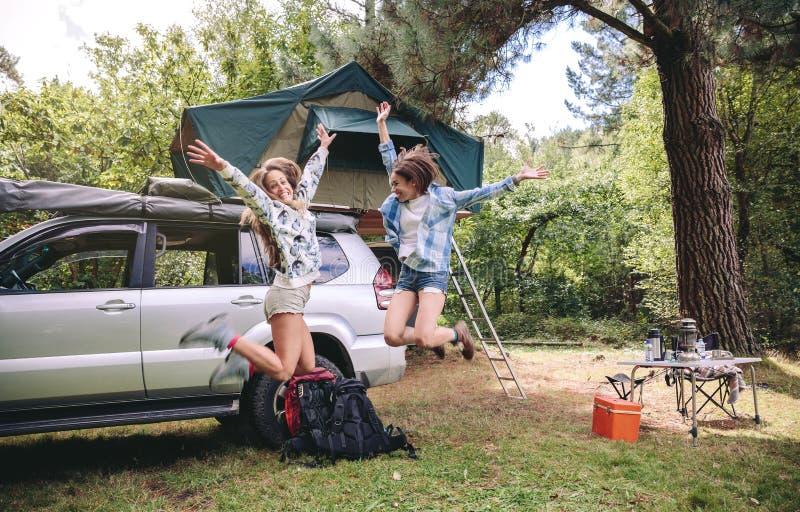 Φίλοι γυναικών που πηδούν στη θέση για κατασκήνωση στο δάσος στοκ φωτογραφίες