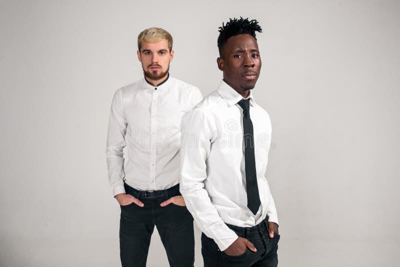 Φίλοι Δύο τύποι στα άσπρα πουκάμισα και τα σκοτεινά εσώρουχα που θέτουν στο στούντιο σε ένα άσπρο υπόβαθρο στοκ εικόνες με δικαίωμα ελεύθερης χρήσης