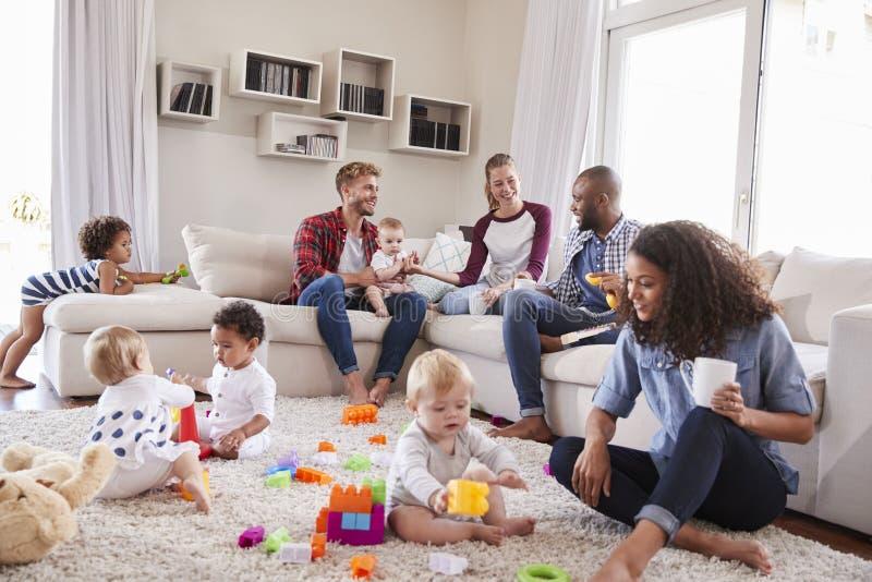 Φίλοι με τα μικρά παιδιά που παίζουν στο πάτωμα στο δωμάτιο συνεδρίασης στοκ εικόνες