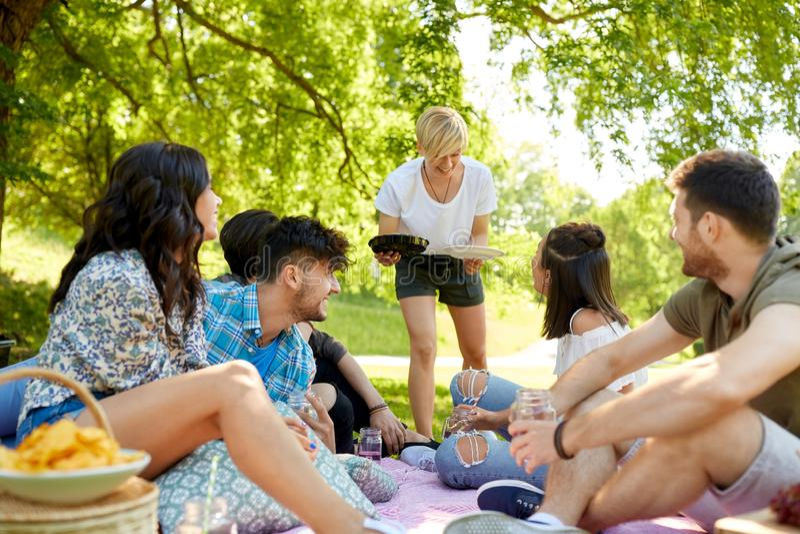 Φίλοι με τα ποτά και τρόφιμα στο πικ-νίκ στο πάρκο στοκ φωτογραφία