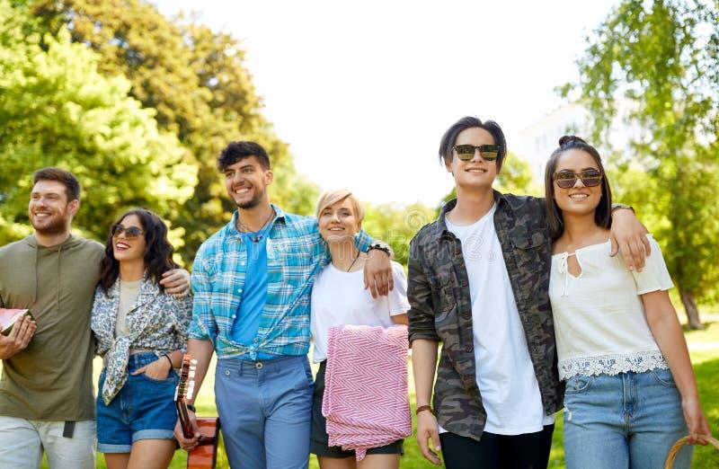 Φίλοι με την κιθάρα που πηγαίνει στο πικ-νίκ στο πάρκο στοκ εικόνες