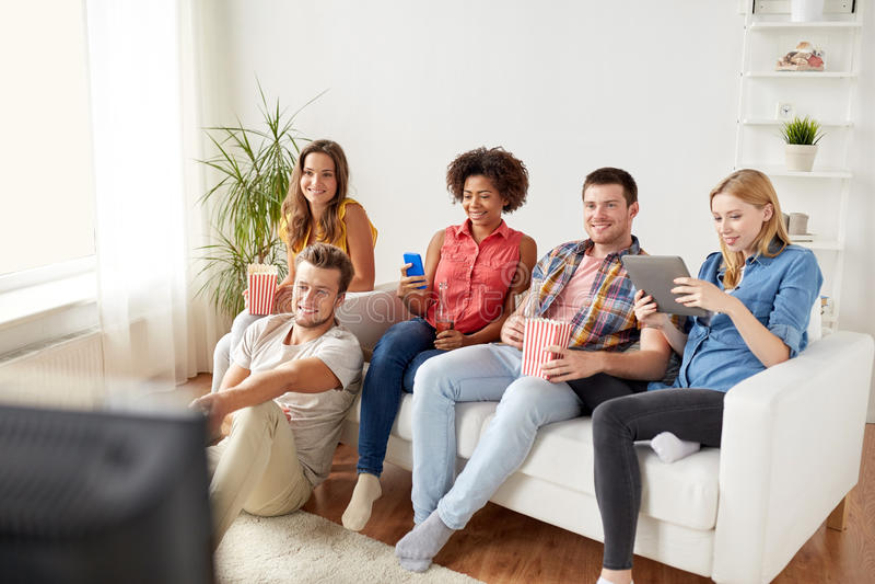 Φίλοι με τις συσκευές και μπύρα που προσέχει τη TV στο σπίτι στοκ φωτογραφία με δικαίωμα ελεύθερης χρήσης