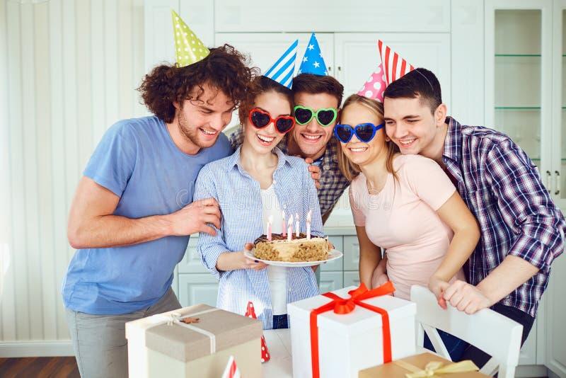 Φίλοι με το κέικ με τα κεριά που γιορτάζουν τα γενέθλια σε ένα κόμμα στοκ εικόνα με δικαίωμα ελεύθερης χρήσης
