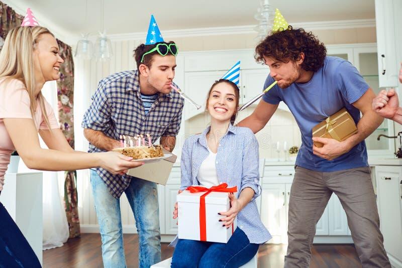Φίλοι με το κέικ με τα κεριά που γιορτάζουν τα γενέθλια σε ένα κόμμα στοκ φωτογραφία