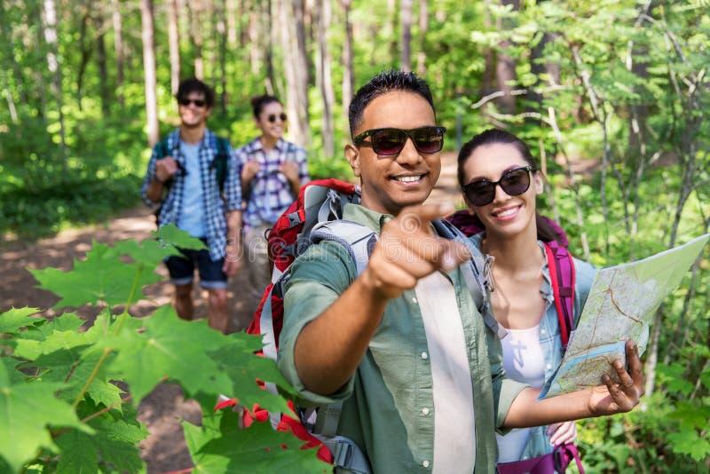 Φίλοι με το χάρτη και σακίδια πλάτης που στο δάσος στοκ εικόνες με δικαίωμα ελεύθερης χρήσης