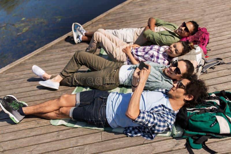 Φίλοι με το smartphone που βρίσκεται στην αποβάθρα λιμνών στοκ φωτογραφίες με δικαίωμα ελεύθερης χρήσης