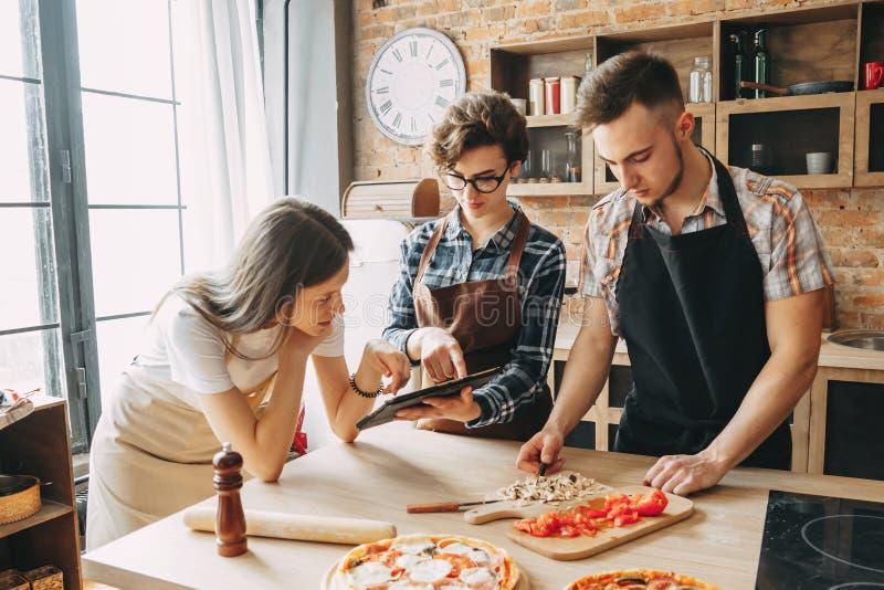 Φίλοι που έχουν τη διασκέδαση που μαγειρεύει μαζί τα τρόφιμα στην κουζίνα Μαγειρικός, τ στοκ φωτογραφία