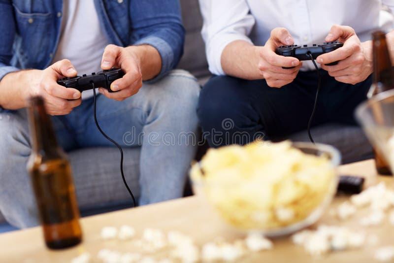 Φίλοι που έχουν τη διασκέδαση στον καναπέ με τα τηλεοπτικά παιχνίδια στοκ εικόνες