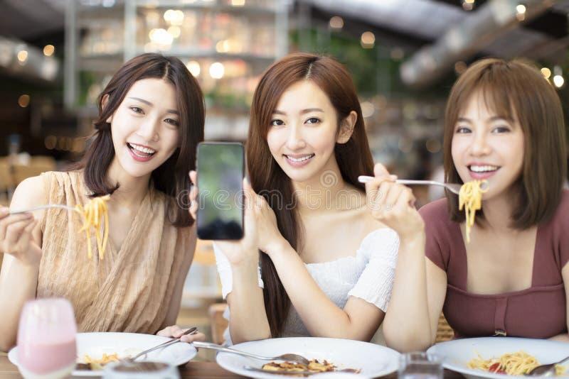 φίλοι που έχουν το γεύμα και που παρουσιάζουν έξυπνο τηλέφωνο στο εστιατόριο στοκ εικόνα