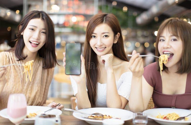 φίλοι που έχουν το γεύμα και που παρουσιάζουν έξυπνο τηλέφωνο στο εστιατόριο στοκ φωτογραφία με δικαίωμα ελεύθερης χρήσης