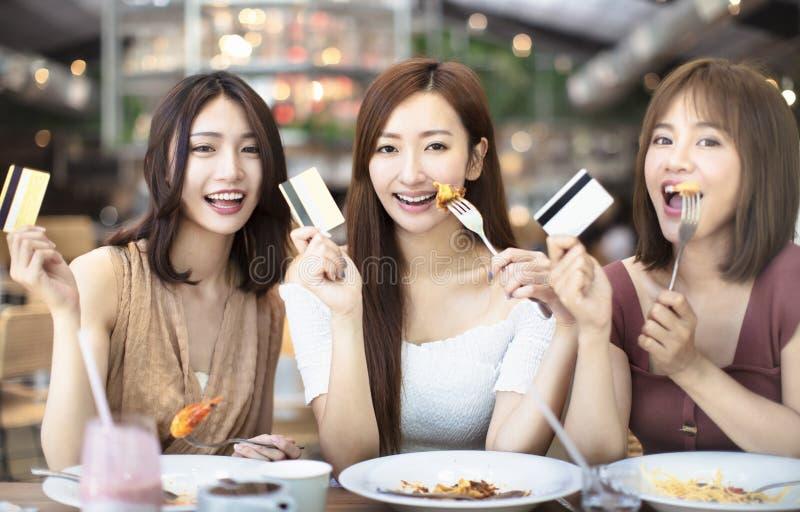 φίλοι που έχουν το γεύμα και που παρουσιάζουν πιστωτική κάρτα στο εστιατόριο στοκ φωτογραφία με δικαίωμα ελεύθερης χρήσης