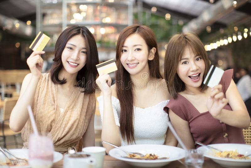 φίλοι που έχουν το γεύμα και που παρουσιάζουν πιστωτική κάρτα στο εστιατόριο στοκ εικόνες