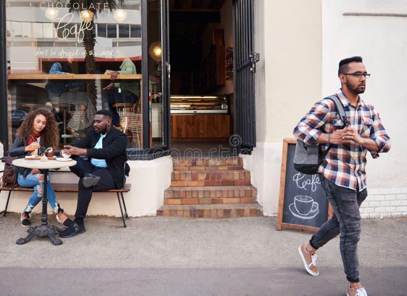 Φίλοι που έχουν το κέικ και τον καφέ μαζί σε έναν καφέ πεζοδρομίων στοκ εικόνα