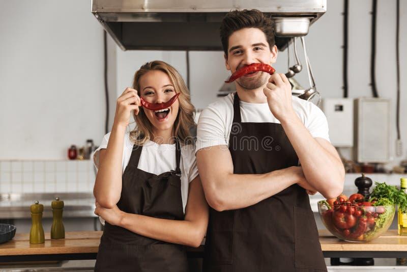 Φίλοι που αγαπούν τους αρχιμάγειρες ζευγών στην κουζίνα που έχει τη διασκέδαση με το πιπέρι ως moustache στοκ εικόνα με δικαίωμα ελεύθερης χρήσης