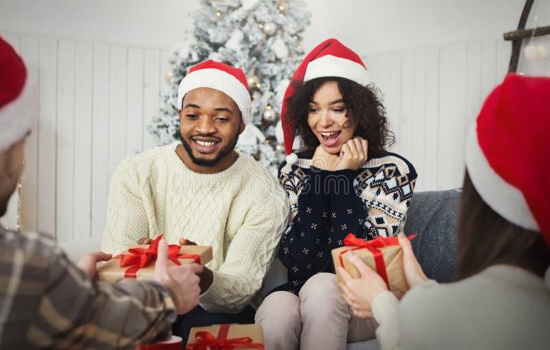 Φίλοι που απολαμβάνουν μοιραμένος τα χριστουγεννιάτικα δώρα στο σπίτι στοκ φωτογραφίες