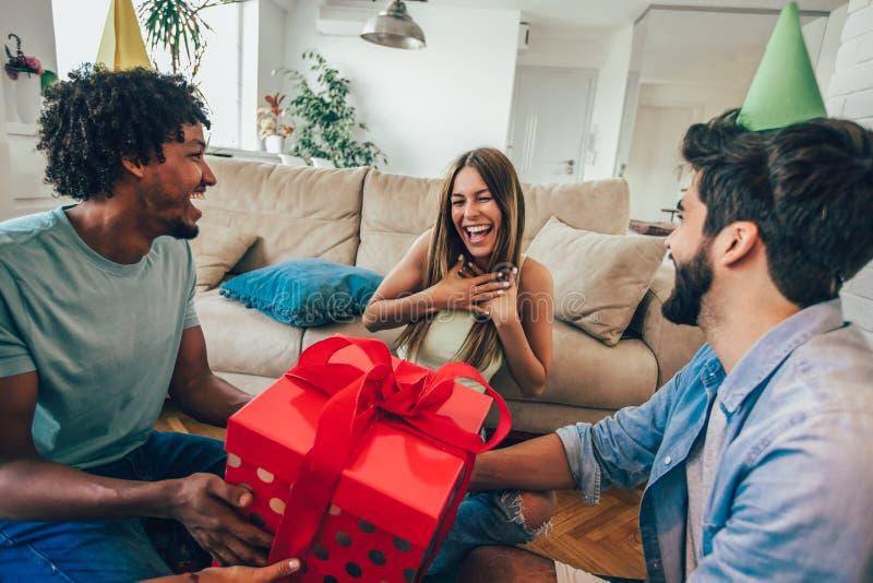 Φίλοι που γιορτάζουν τα γενέθλια και που δίνουν το δώρο σε ένα κορίτσι στοκ εικόνες