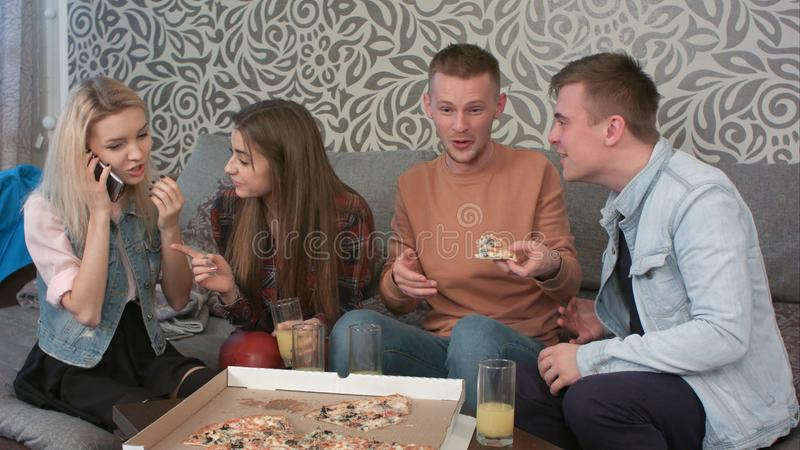Φίλοι που κάθονται στο διαμέρισμα και που μιλούν στο κινητό τηλέφωνο στοκ εικόνα