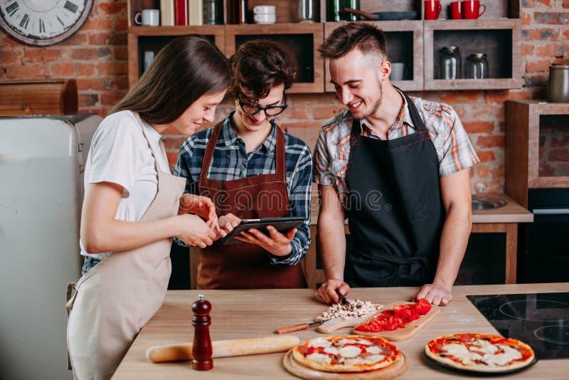 Φίλοι που μαγειρεύουν από κοινού Ομάδα νέων που προετοιμάζουν το γεύμα στοκ φωτογραφία με δικαίωμα ελεύθερης χρήσης
