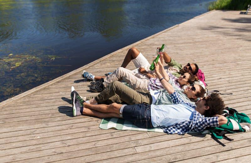 Φίλοι που πίνουν την μπύρα και το μηλίτη στην αποβάθρα λιμνών στοκ εικόνες με δικαίωμα ελεύθερης χρήσης