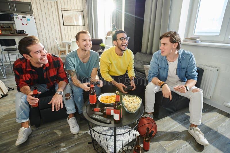 Φίλοι που παίζουν τα ψηφιακά παιχνίδια στο σπίτι στοκ εικόνες