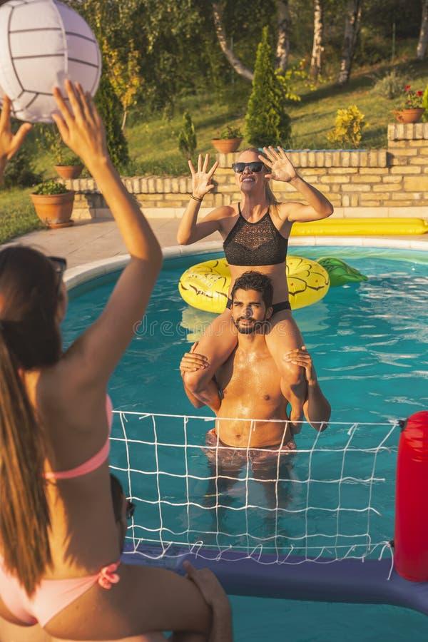 Φίλοι που παίζουν την πετοσφαίριση σε μια πισίνα στοκ φωτογραφία με δικαίωμα ελεύθερης χρήσης