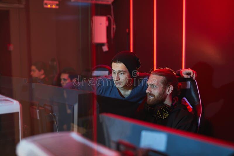 Φίλοι που παίζουν το παιχνίδι στον υπολογιστή στη λέσχη παιχνιδιών PC στοκ φωτογραφίες
