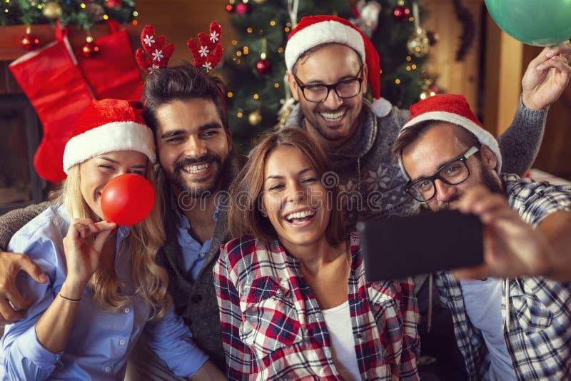 Φίλοι που παίρνουν τα Χριστούγεννα selfies στοκ εικόνες