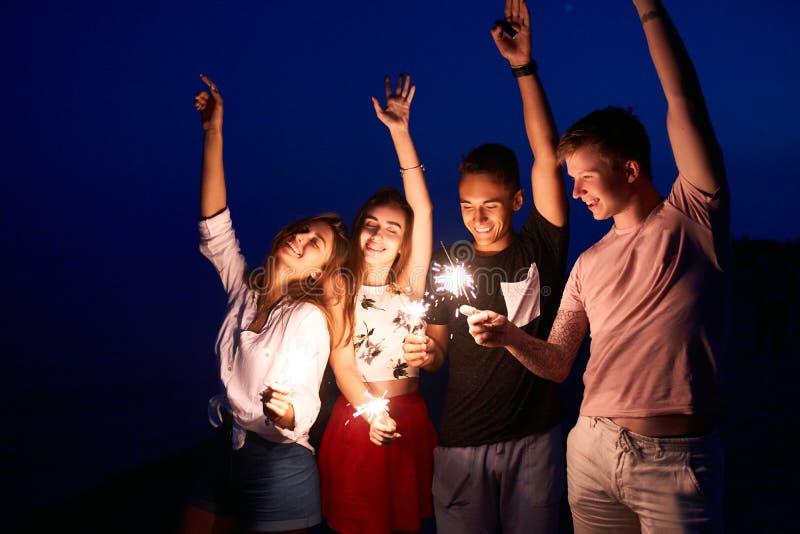 Φίλοι που περπατούν, που χορεύουν και που έχουν τη διασκέδαση κατά τη διάρκεια του κόμματος νύχτας στην παραλία με τα φω'τα της Β στοκ εικόνα με δικαίωμα ελεύθερης χρήσης