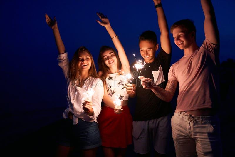 Φίλοι που περπατούν, που χορεύουν και που έχουν τη διασκέδαση κατά τη διάρκεια του κόμματος νύχτας στην παραλία με τα φω'τα της Β στοκ εικόνες