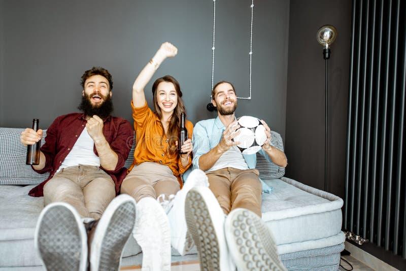 Φίλοι που προσέχουν τον αγώνα ποδοσφαίρου στο σπίτι στοκ φωτογραφίες