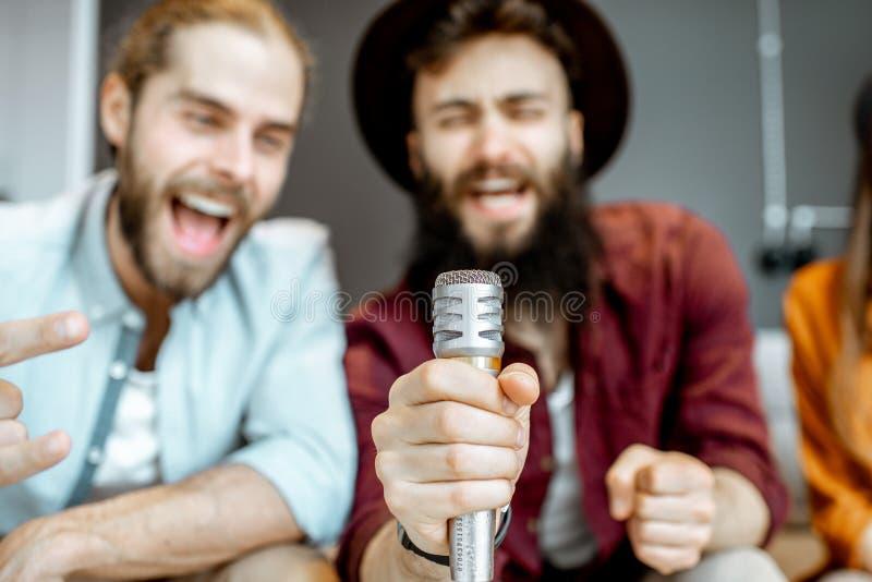 Φίλοι που τραγουδούν στο σπίτι στοκ φωτογραφίες