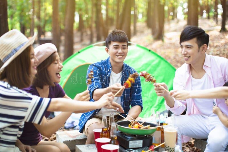 Φίλοι που τρώνε τη σχάρα και που έχουν τη διασκέδαση ενθαρρυντική στοκ εικόνα
