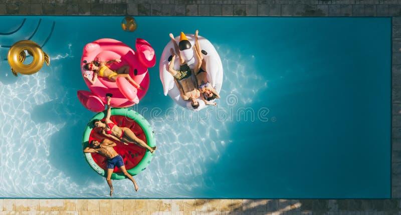 Φίλοι που χαλαρώνουν στα διογκώσιμα στρώματα στη λίμνη στοκ φωτογραφία