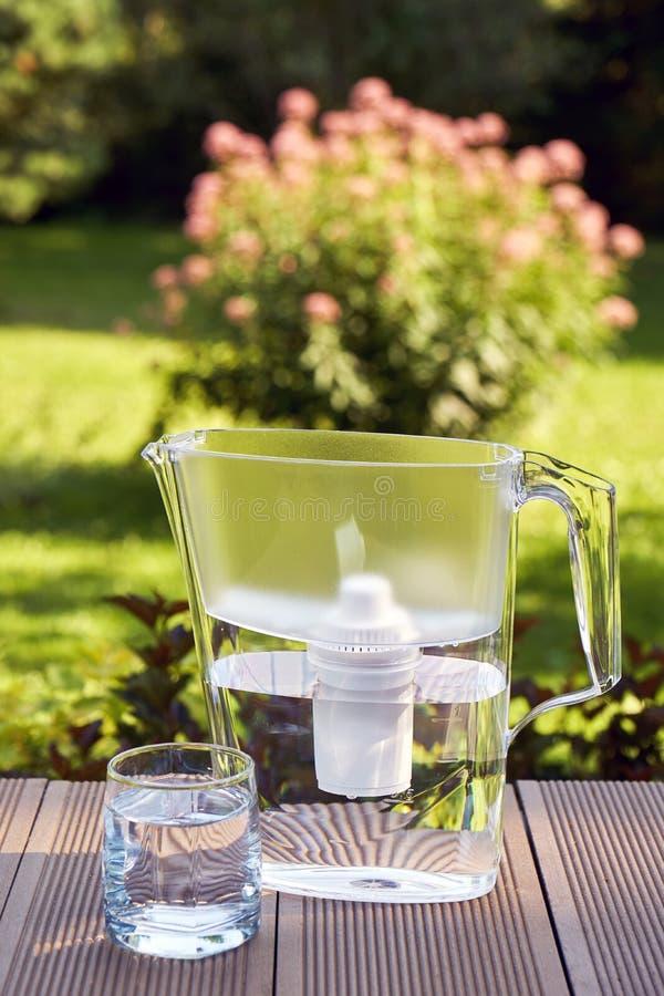 Φίλτρο νερού και ένα καθαρό ποτήρι ενός σαφούς νερού στο υπόβαθρο θερινών κήπων στοκ φωτογραφία με δικαίωμα ελεύθερης χρήσης