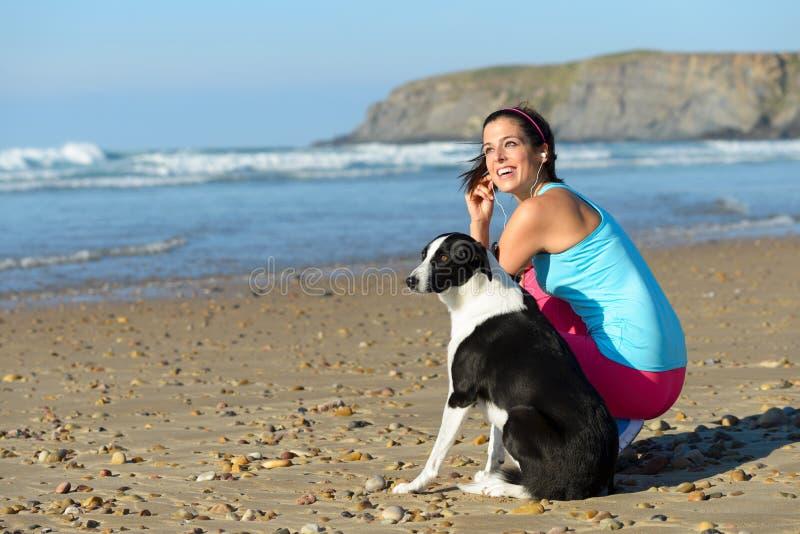 Φίλαθλα γυναίκα και σκυλί στην παραλία στοκ εικόνες με δικαίωμα ελεύθερης χρήσης